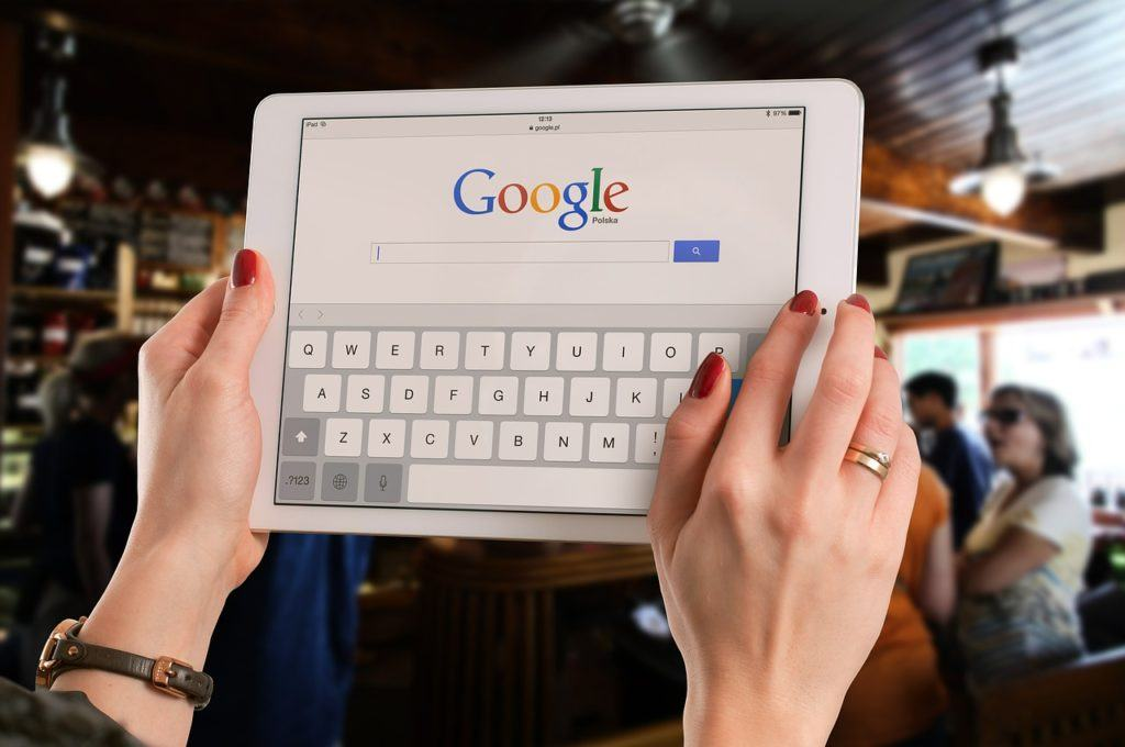 female hands on an ipad with Google search loaded