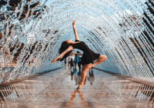 woman dancing under a fountain of water