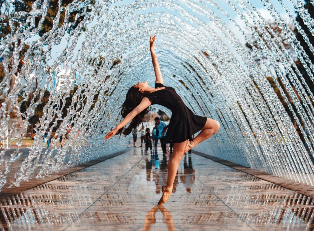 a woman dancing under a fountain